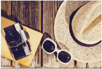 Holiday fraud - image of sunhat, sunglasses, camera & book